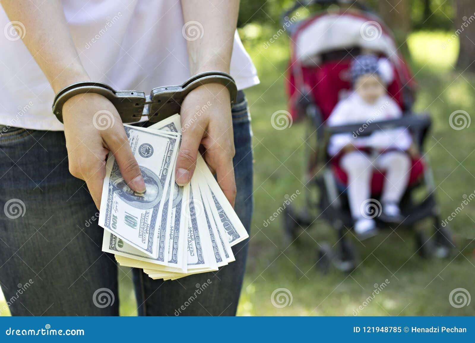 Una ragazza sta tenendo i dollari in manette contro il contesto di un bambino in un trasporto, arresto dei soldi, trafficante nei