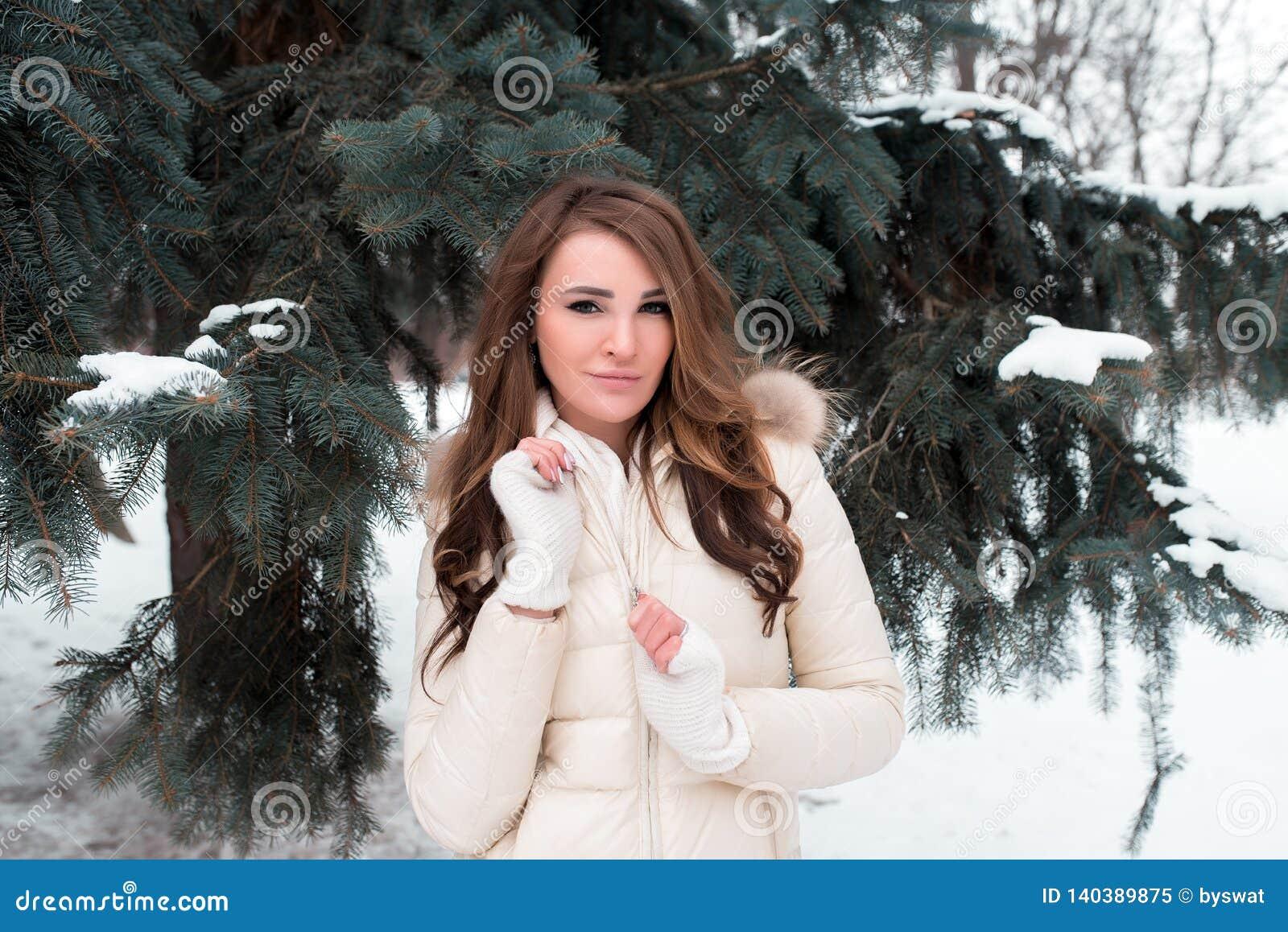 Una ragazza in un parco di inverno su un fondo degli alberi verdi, in un piumino bianco con capelli marroni lunghi, una donna fel