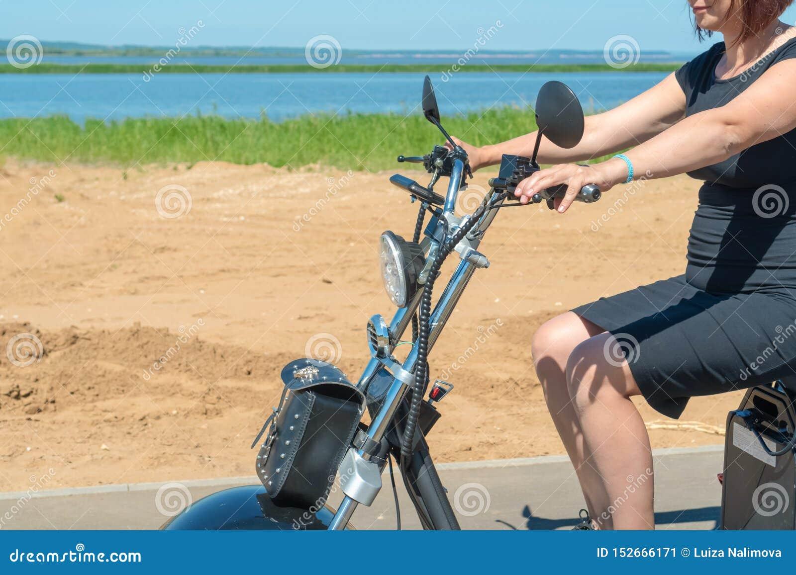 Una ragazza in un vestito nero con capelli rossi che conducono il suo motociclo elettrico a tre ruote lungo la spiaggia un giorno