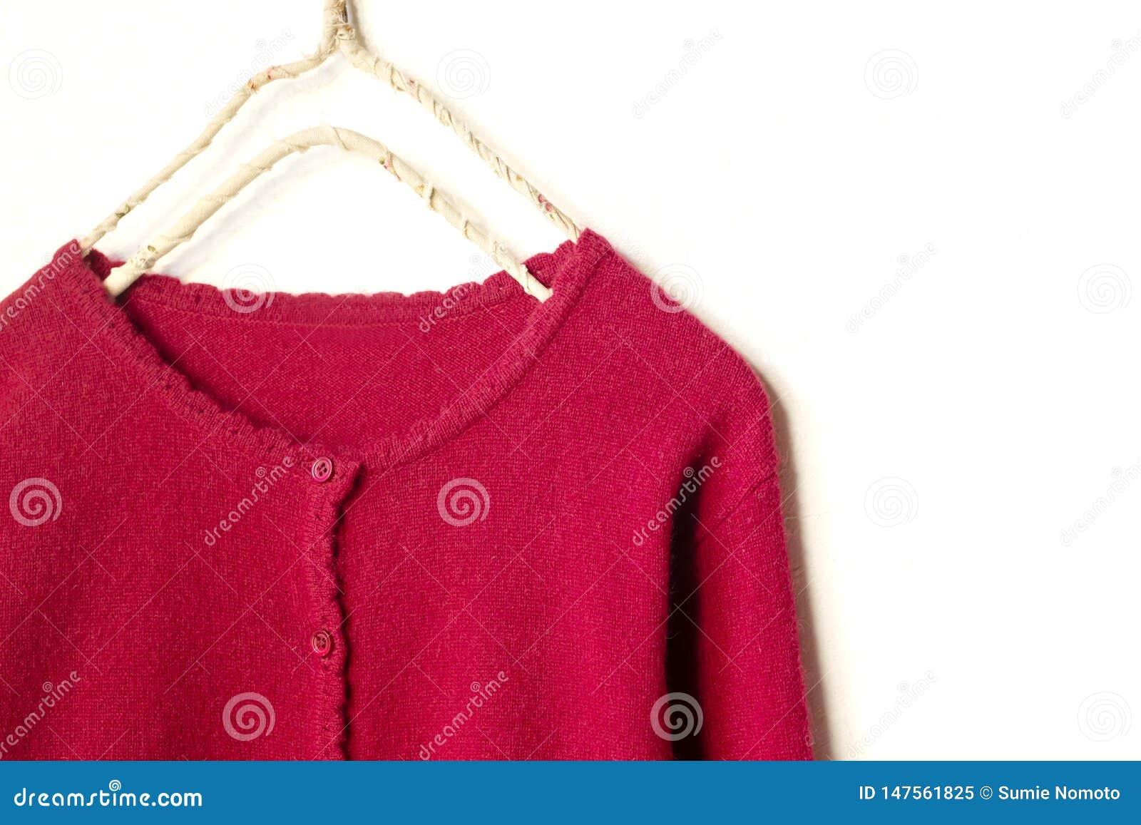 Una rebeca en la ejecuci?n roja en la suspensi?n de ropa en el fondo blanco