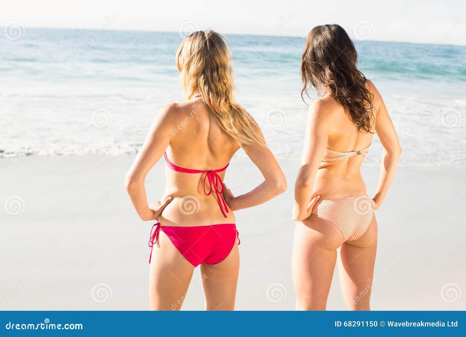 Una retrovisione di due donne in bikini che sta sulla spiaggia