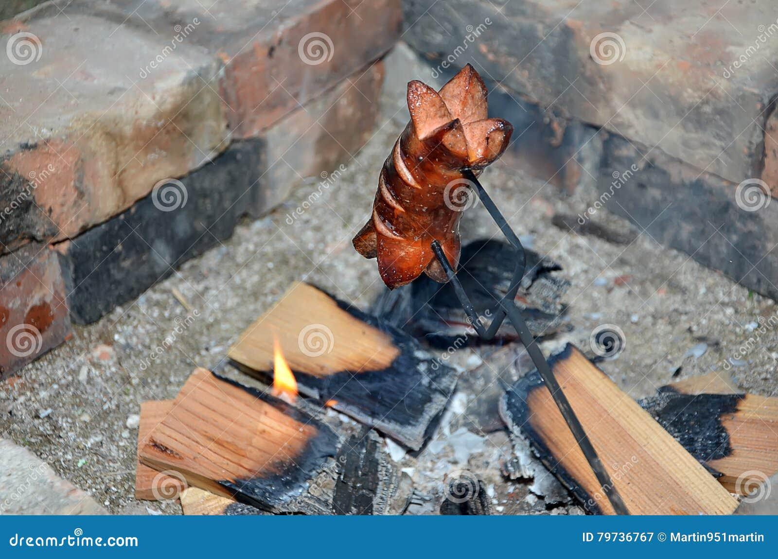 Una salchicha de asado a la parilla sobre un fuego en verano