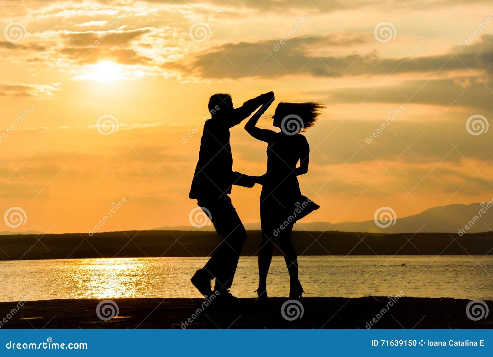 Una salsa del baile de los pares en la puesta del sol por un agua