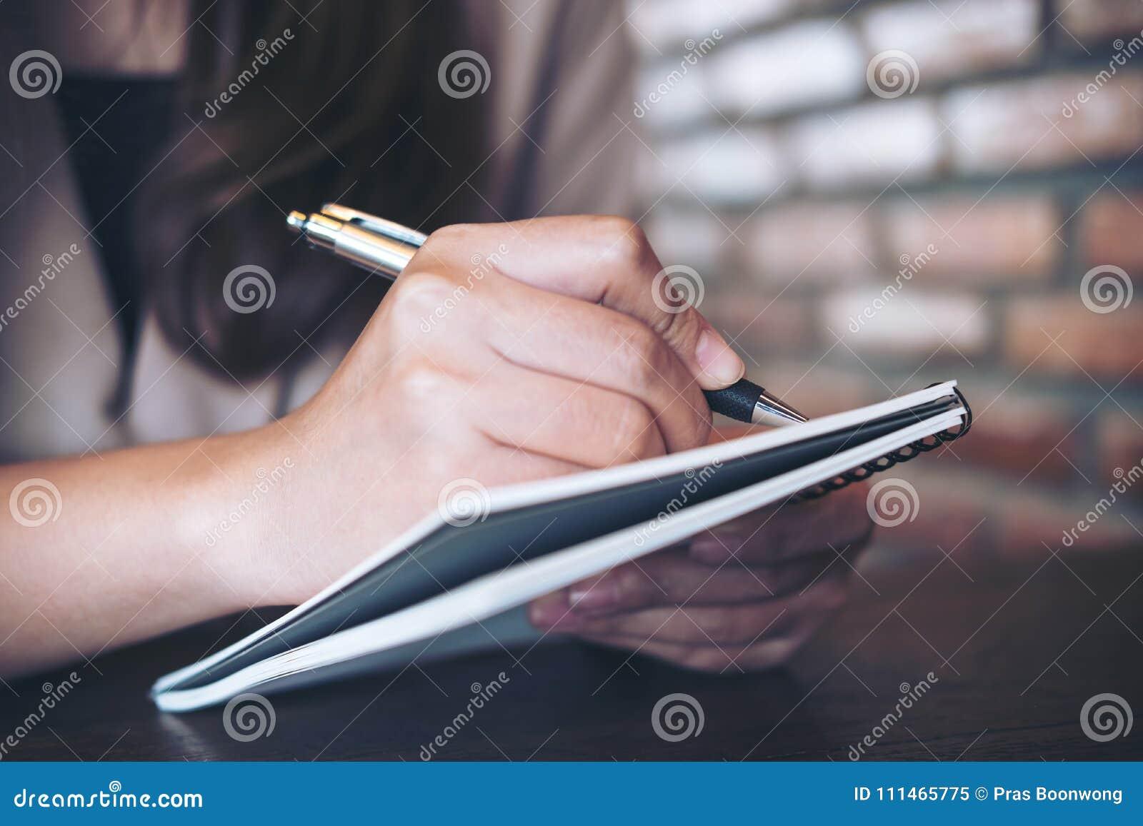 Una scrittura della donna di affari e prendere nota sul taccuino in ufficio