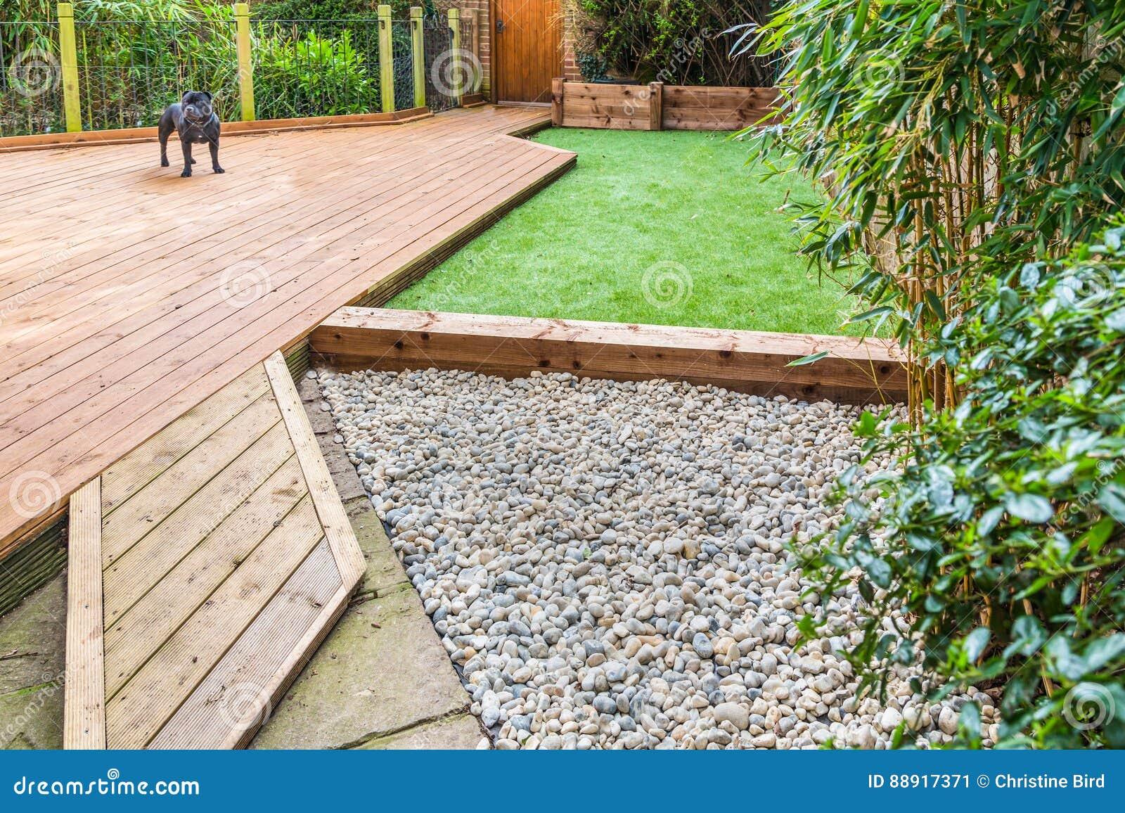 Una sección de un jardín residntial, yarda con decking de madera,