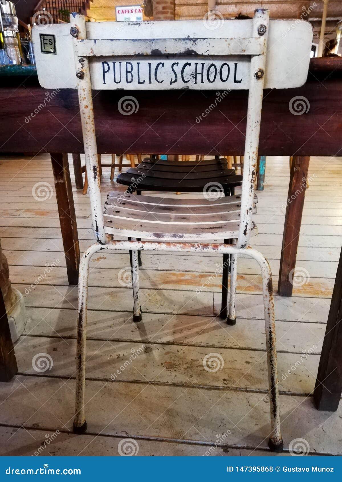 Una silla vieja agradable del estudio delante de un escritorio con la escuela p?blica de las palabras impresa en la parte posteri