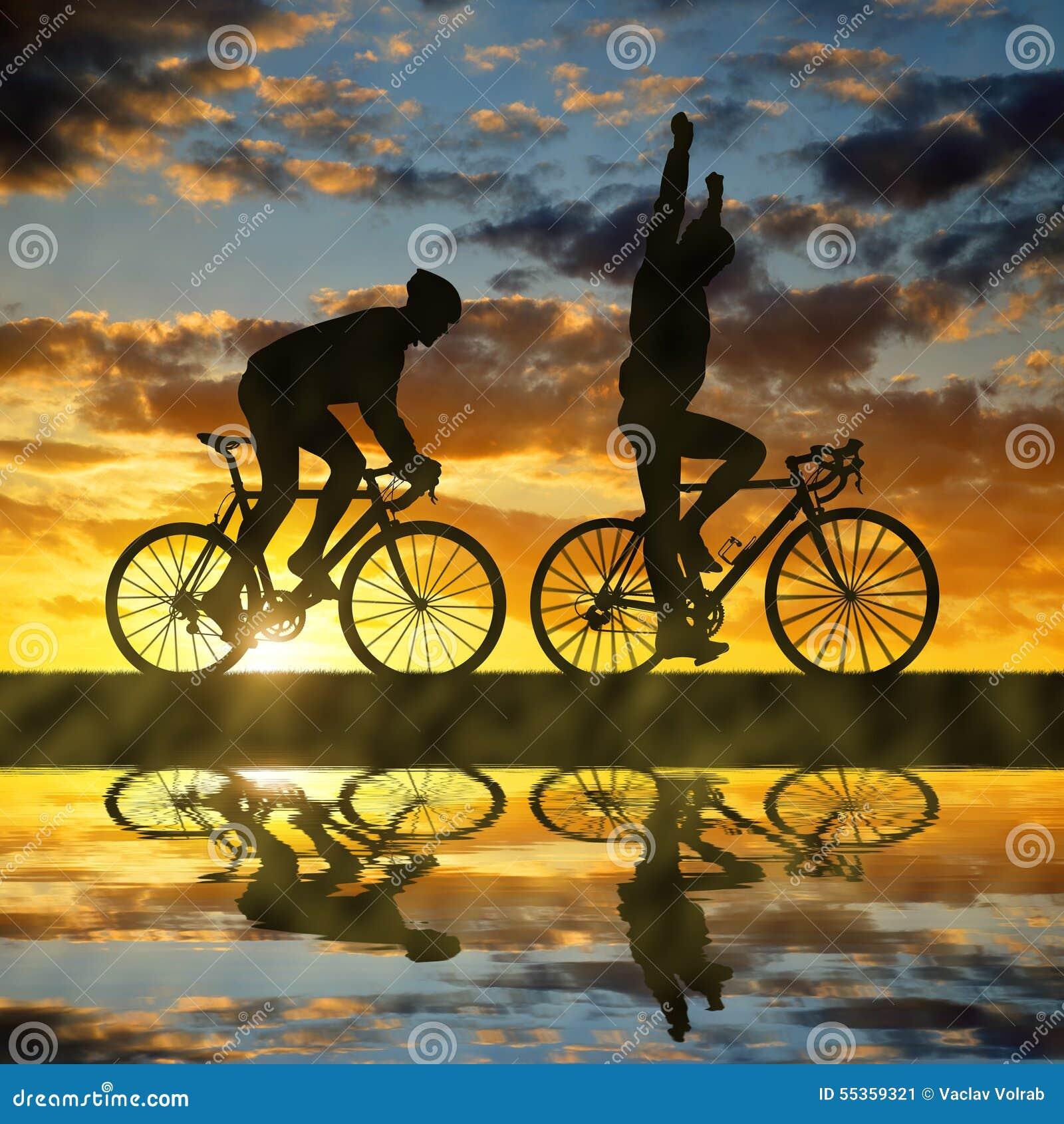 Una siluetta di due ciclisti che guidano una strada bike