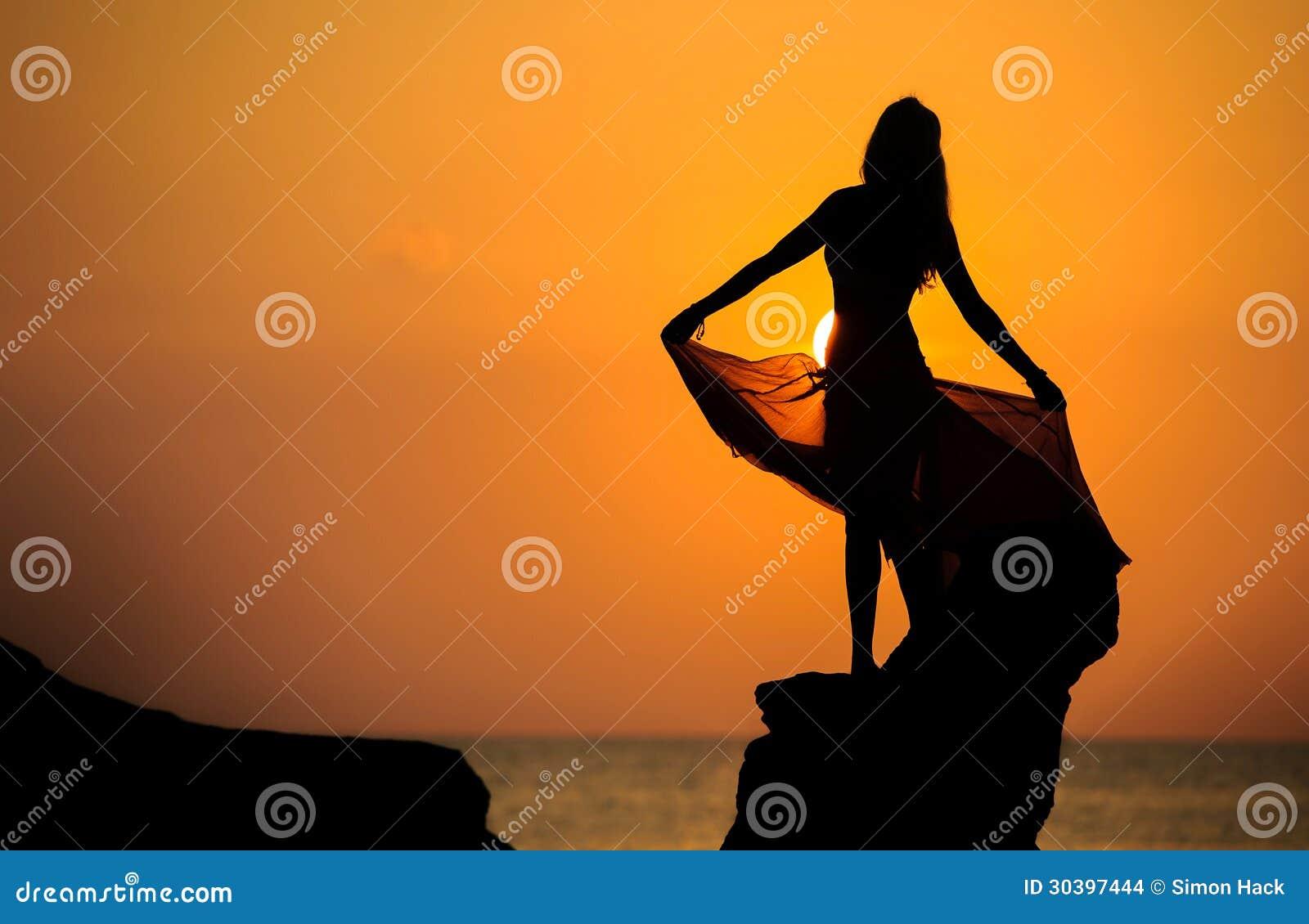 Una siluetta di una ragazza su roccia al tramonto 1 - Immagine di una ragazza a colori ...