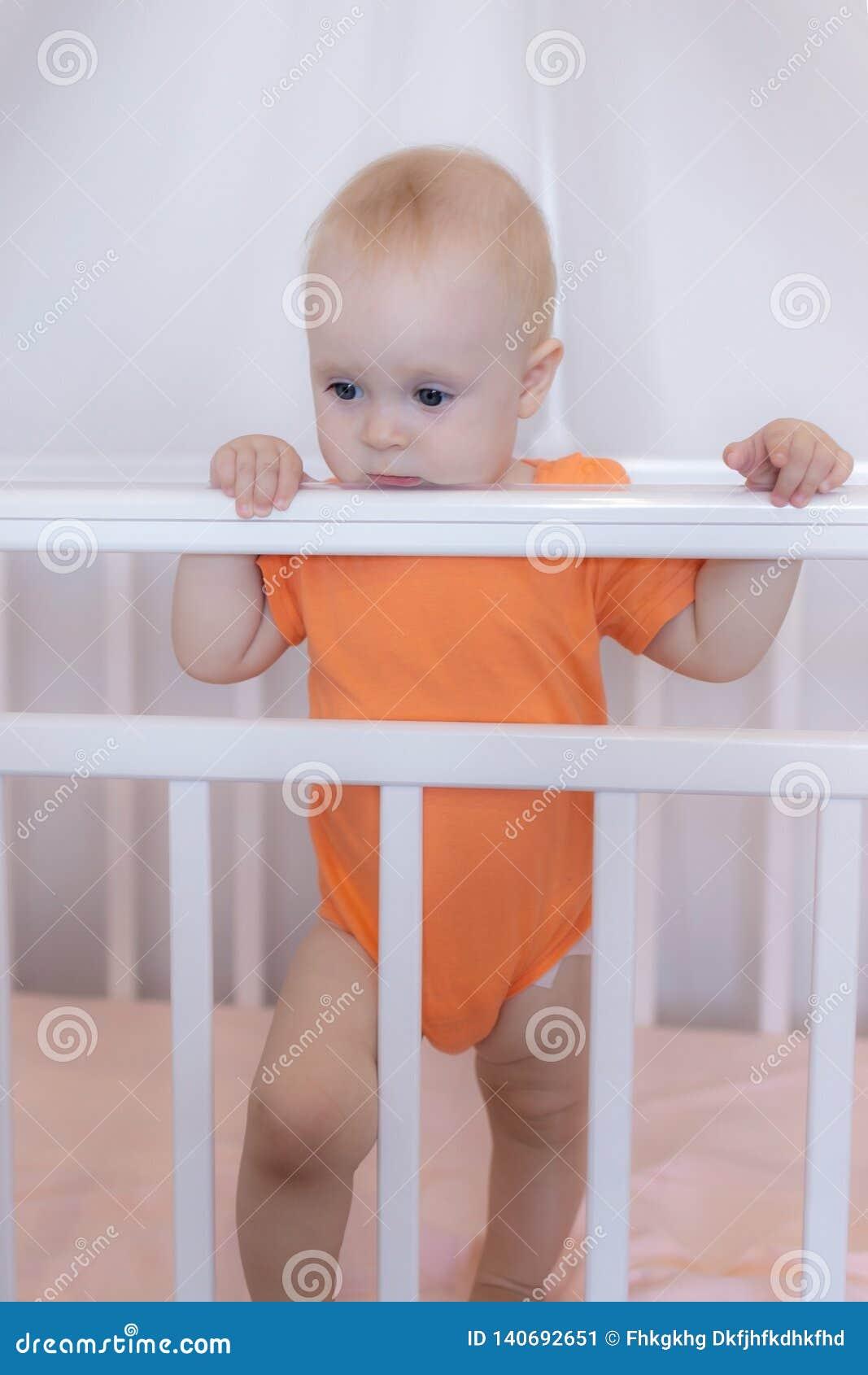Una situación infantil linda del bebé en un pesebre en una escena rosada del dormitorio
