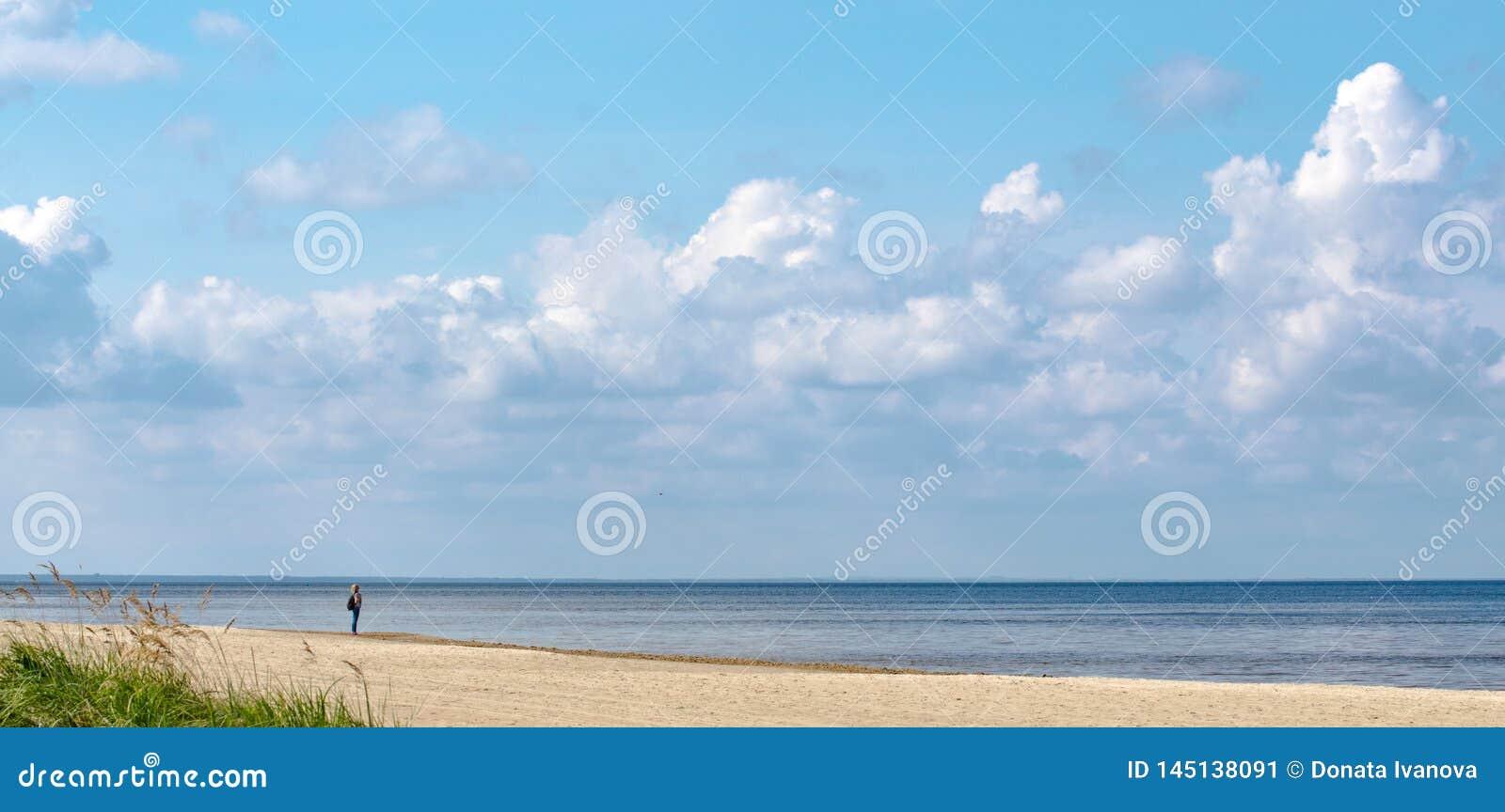 Una situación sola de la mujer en la arena en la orilla del mar Báltico y de mirar la línea del horizonte