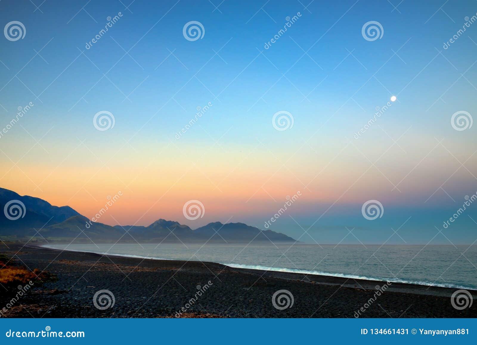 Una spiaggia strabiliante Ciò era Kaikoura contenuto, Nuova Zelanda Era primo mattino ed il sol levante splende un arancia dorata