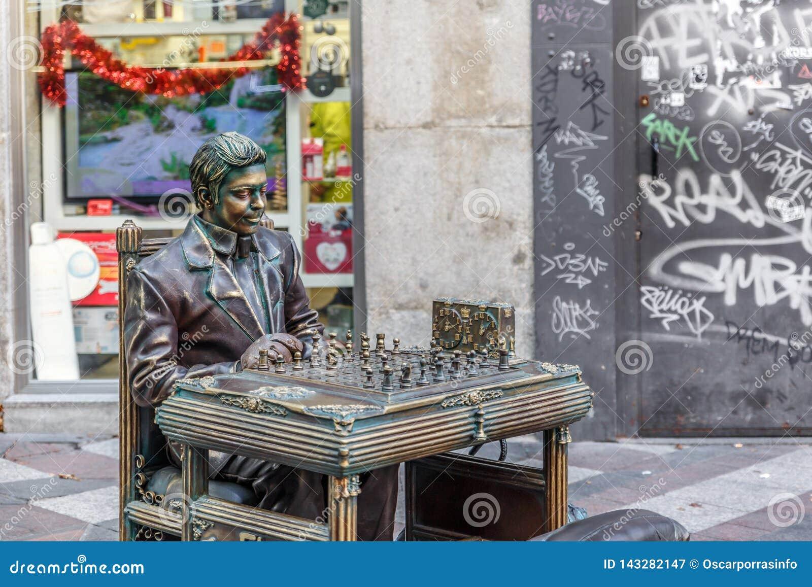 Una statua dell uomo gioca il giocatore di scacchi, fingente di essere tutto il bronzo