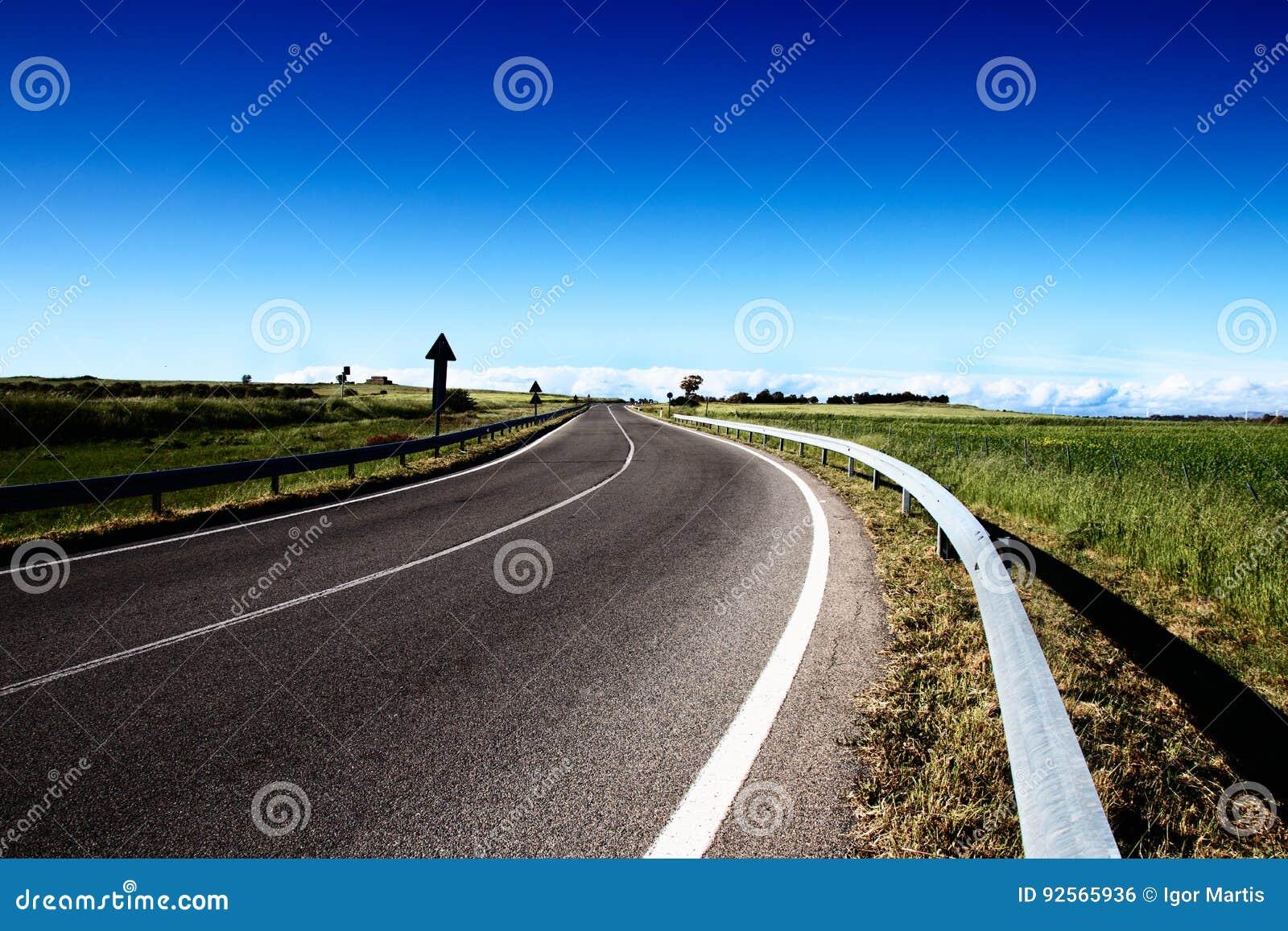 Una strada vuota nelle campagne con un cielo blu