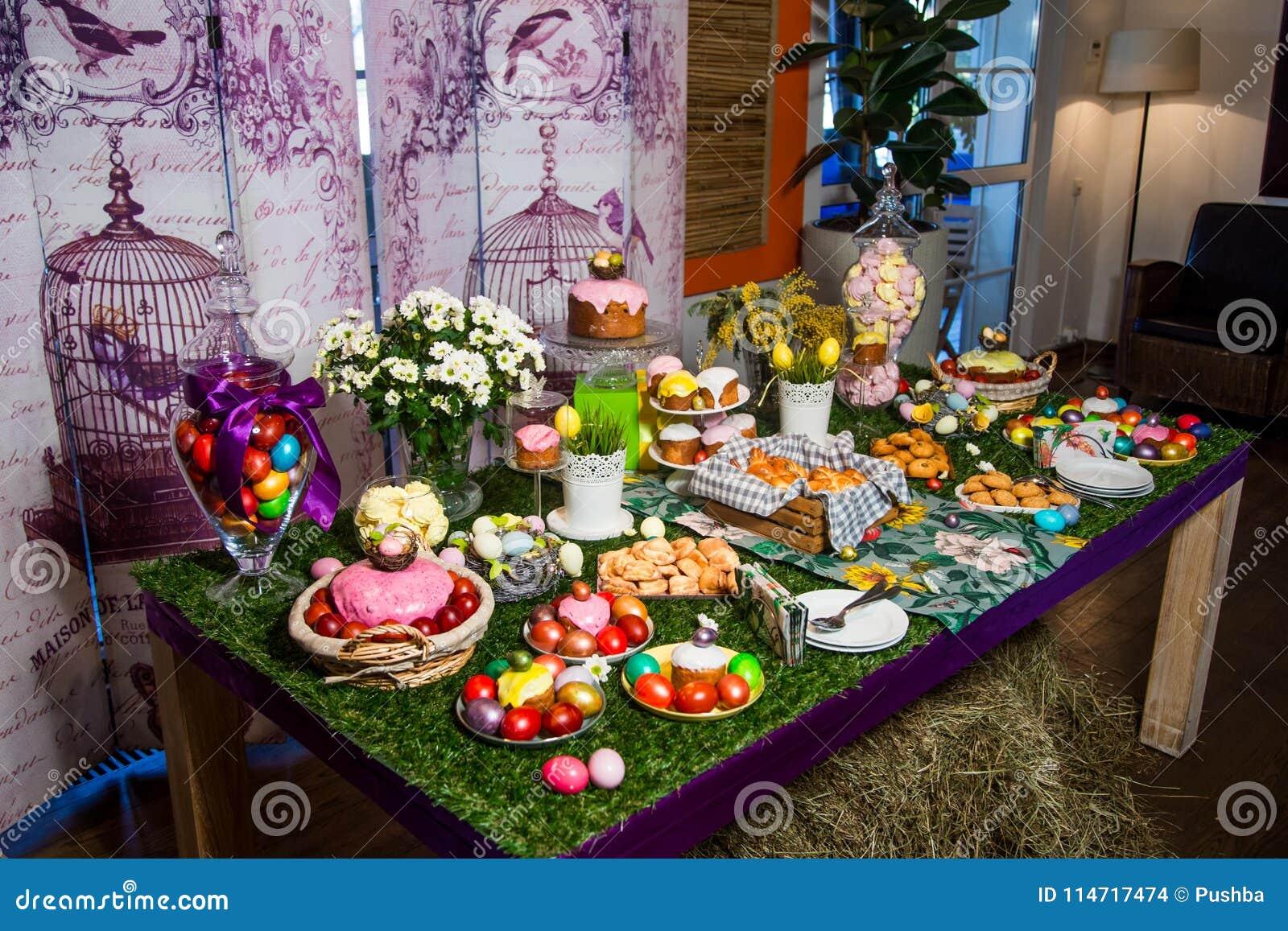 Una tabla de madera con un mantel herboso y las invitaciones de Pascua: huevos, tortas, huevos de chocolate, merengues