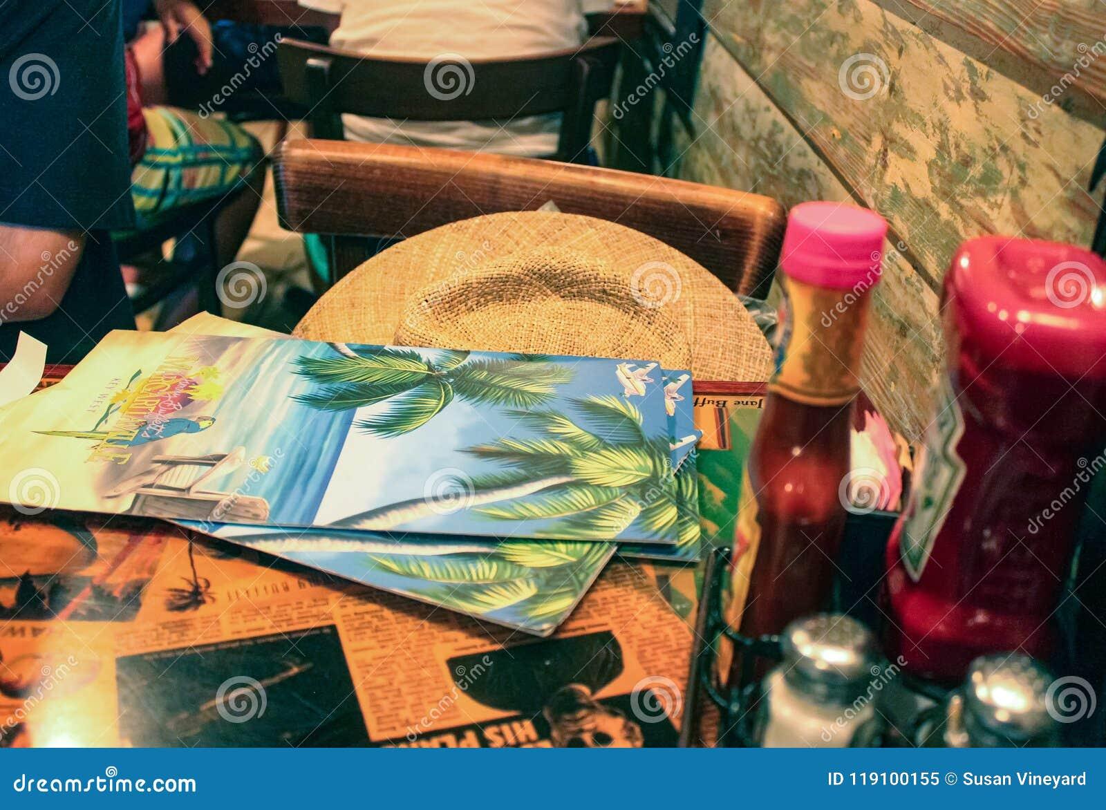 Una tabla en Margaritaville con menús y un sombrero y condimentos Key West la Florida los E.E.U.U.