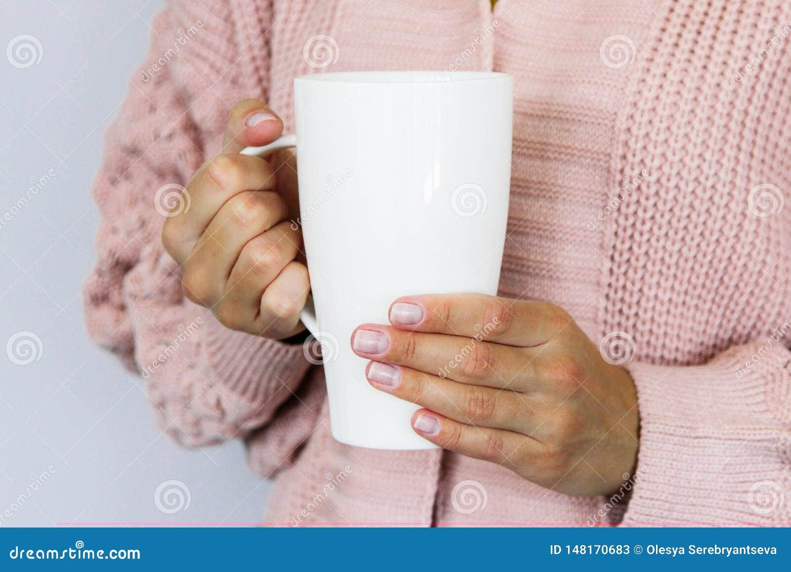 Una taza blanca grande para el caf? o el t? en las manos de una mujer joven vestida en una rebeca hecha punto del color del meloc