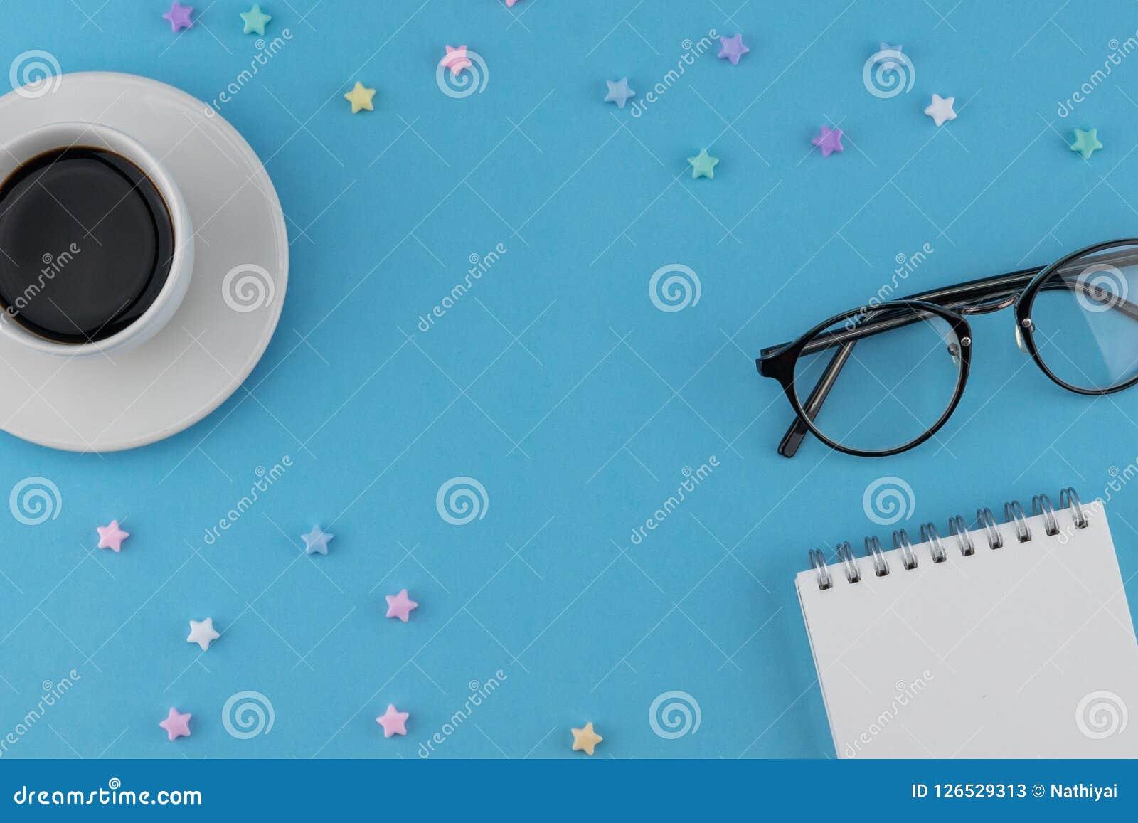 Una taza de café, de cuaderno en blanco y de lentes