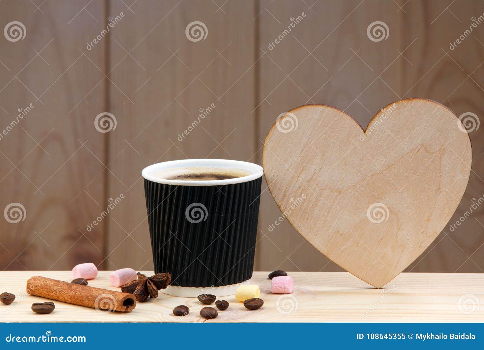 Una taza de café en un estante de madera, con canela, anís, los granos de café y la melcocha