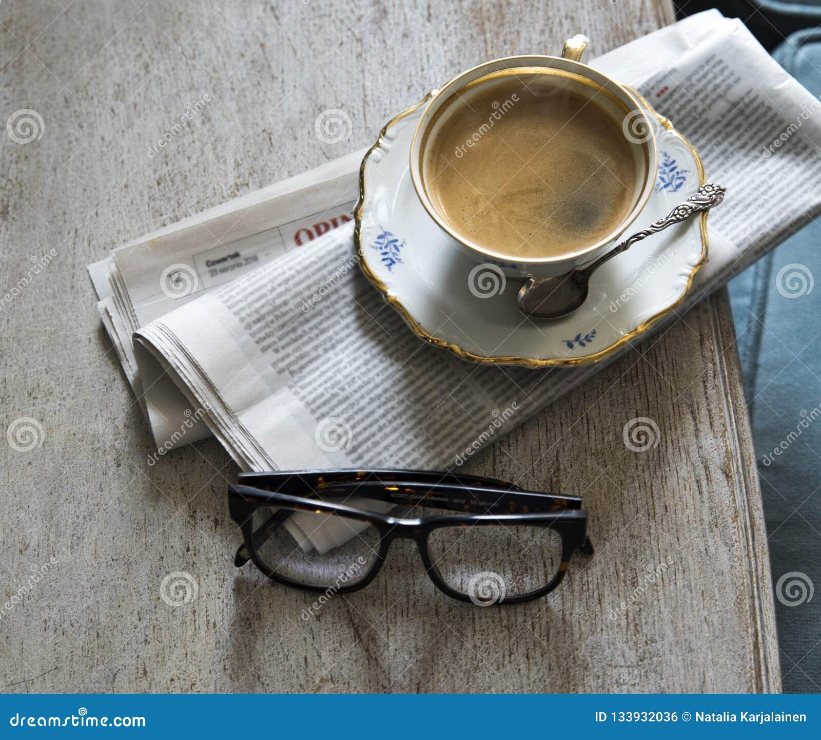 Una taza de café fuerte aromático en un platillo con una cuchara del vintage Periódico y vidrios en la tabla