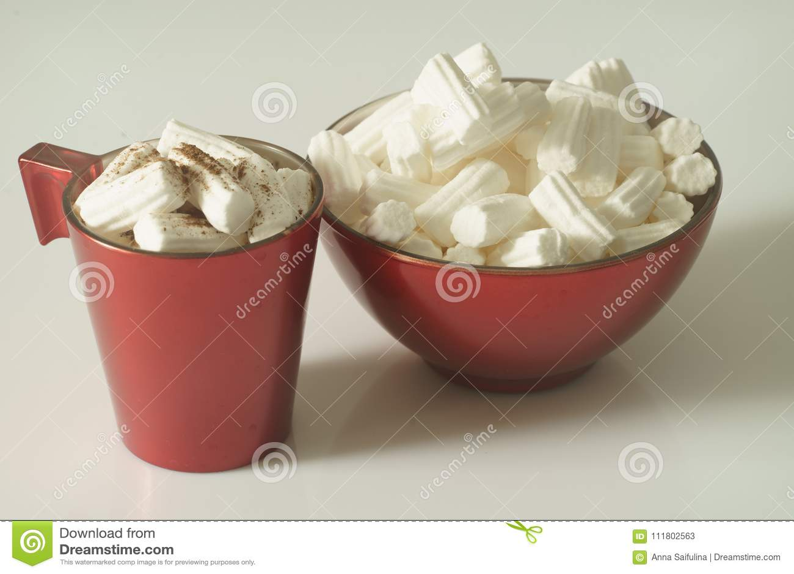 Una taza de café o de chocolate caliente con melcochas y una placa roja en un fondo blanco Cierre para arriba Foto de la Navidad
