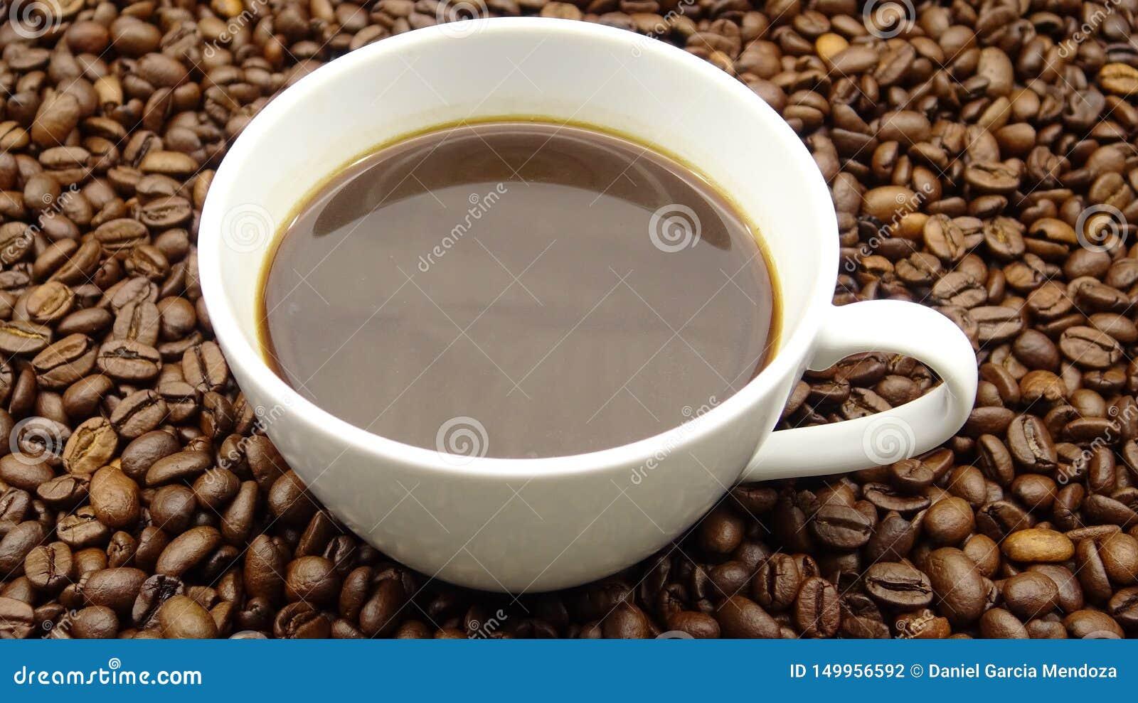 Una taza de café sólo sobre los granos de café asados