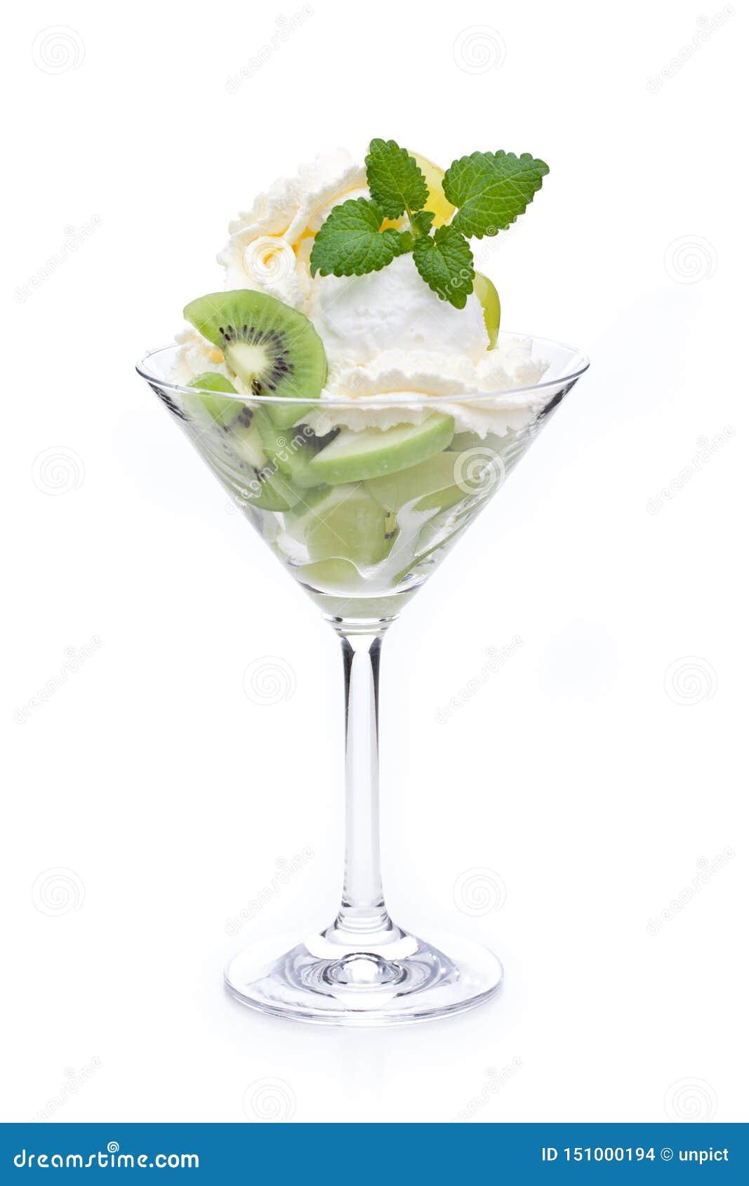 Una taza de helado del limón adornado con los kiwis y las hojas de menta