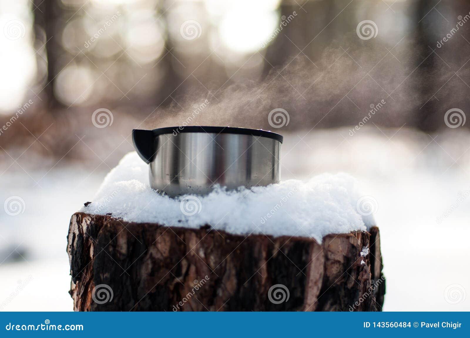 Una taza de soportes calientes del té en un tocón nevado en el invierno, frío, bosque del pino