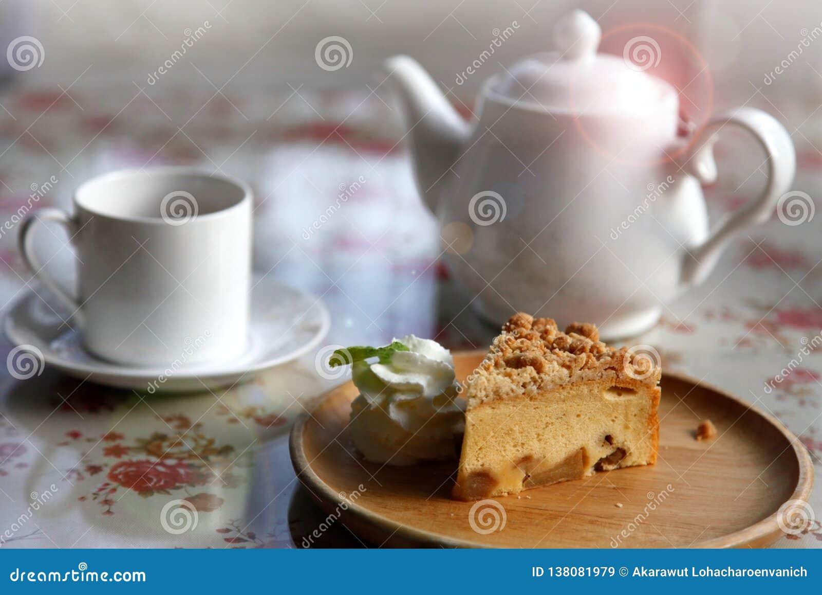 Una taza de té con la tarta hecha en casa de la manzana para el bocado de la tarde con estilo acogedor que vive en casa inglesa d