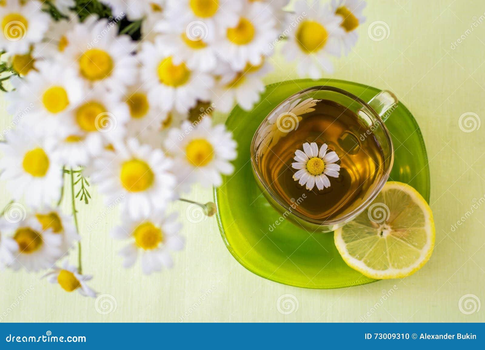 Una taza de té de manzanilla y un ramo de margaritas
