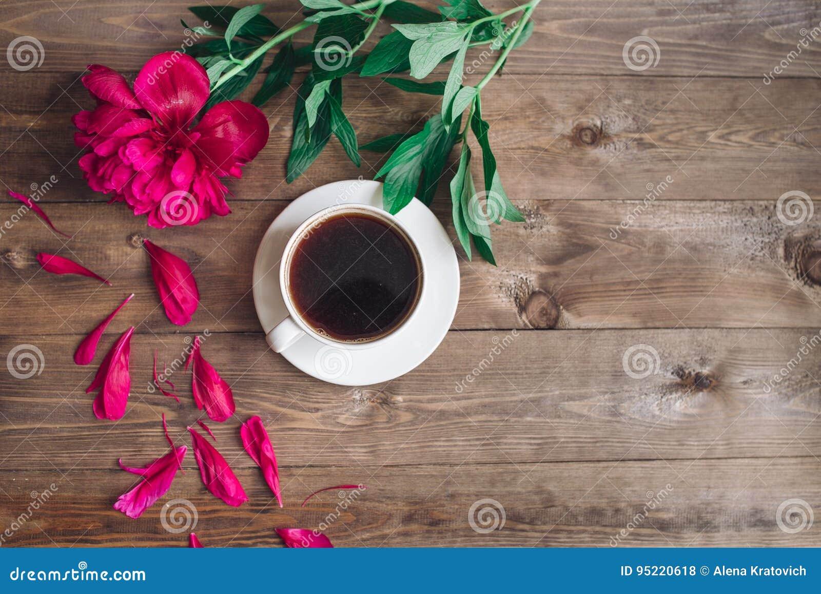 Una taza del café, modelo rojo de las peonías en fondo de madera Buenos días ` S de las mujeres o fondo del día del ` s de la mad