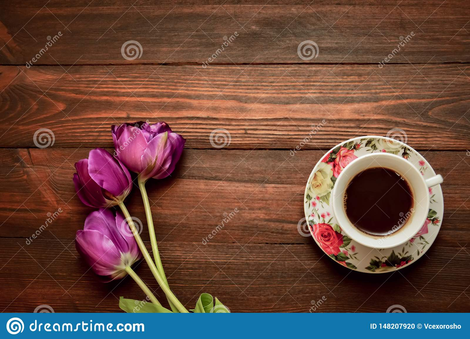 Una tazza di caff? o un t? su un piattino sta su un fondo di legno, tulipani porpora si trover? dopo