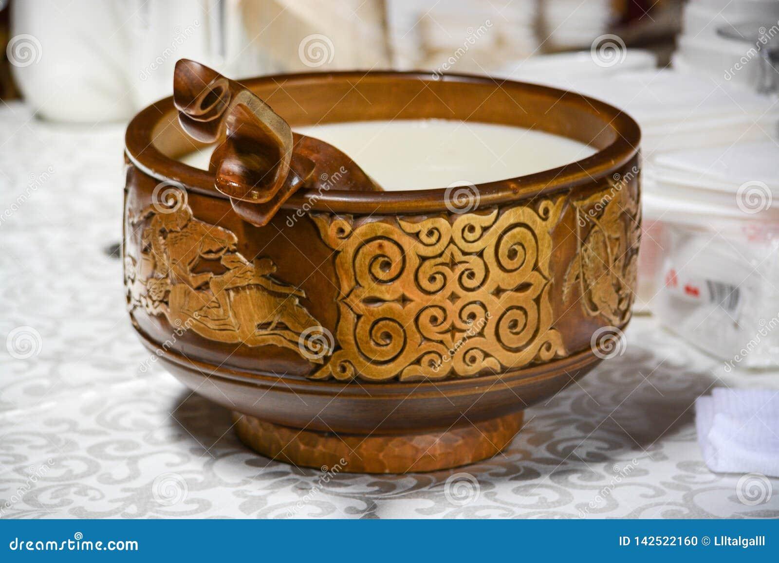 Una tazza di legno con la siviera di un nomade Il latte è versato nella tazza Eredità culturale della gente kazaka