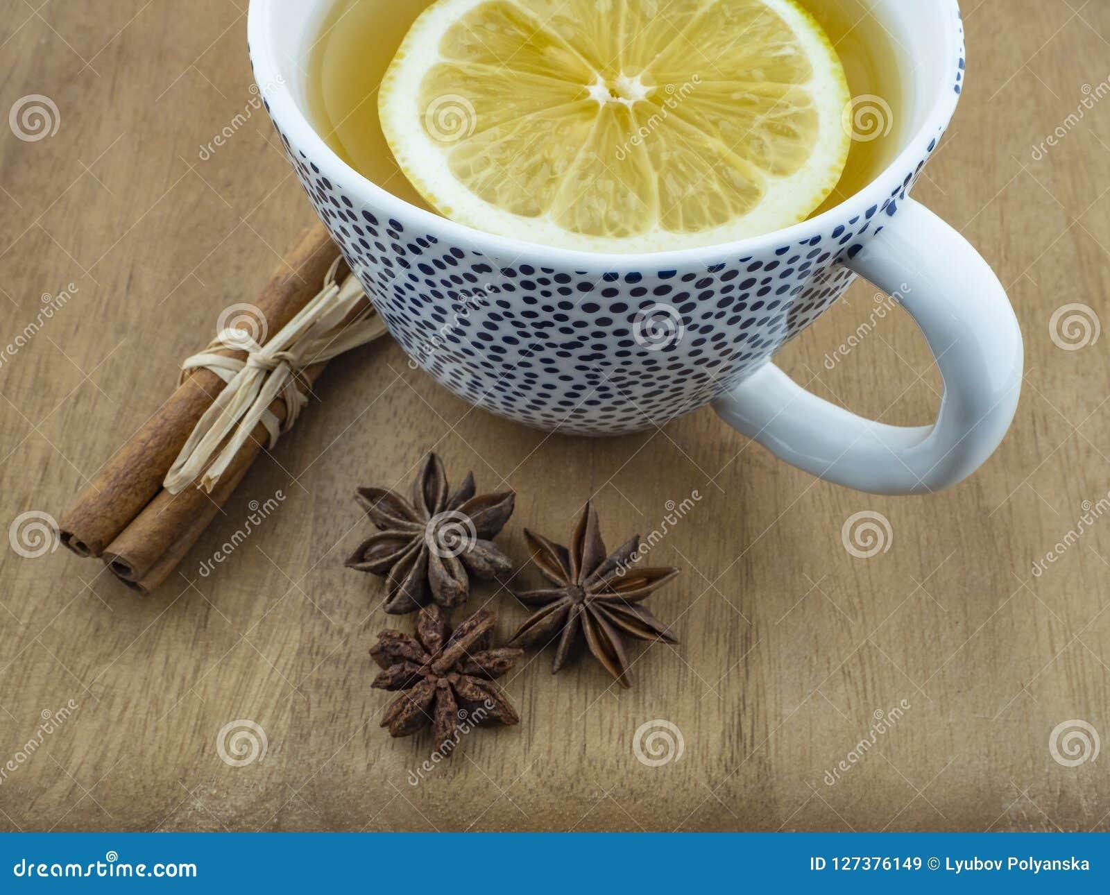 Una tazza di tè verde e di un cuneo di limone su una tavola di legno con i bastoni e l anice di cannella fiorisce