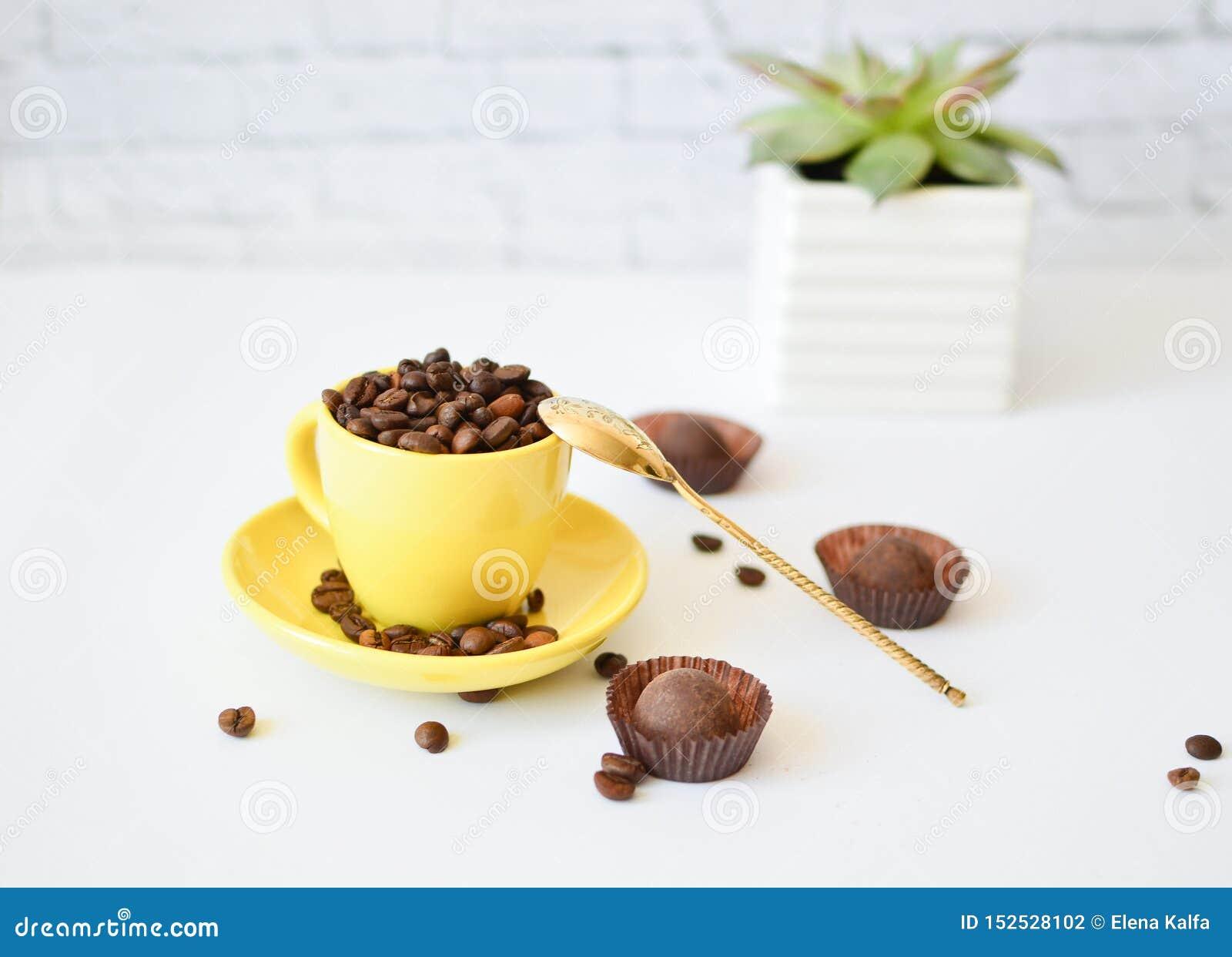 Una tazza gialla con i chicchi di caffè naturali, su un fondo bianco e su un cioccolato Cucchiaio del vinile Concetto del caff? d