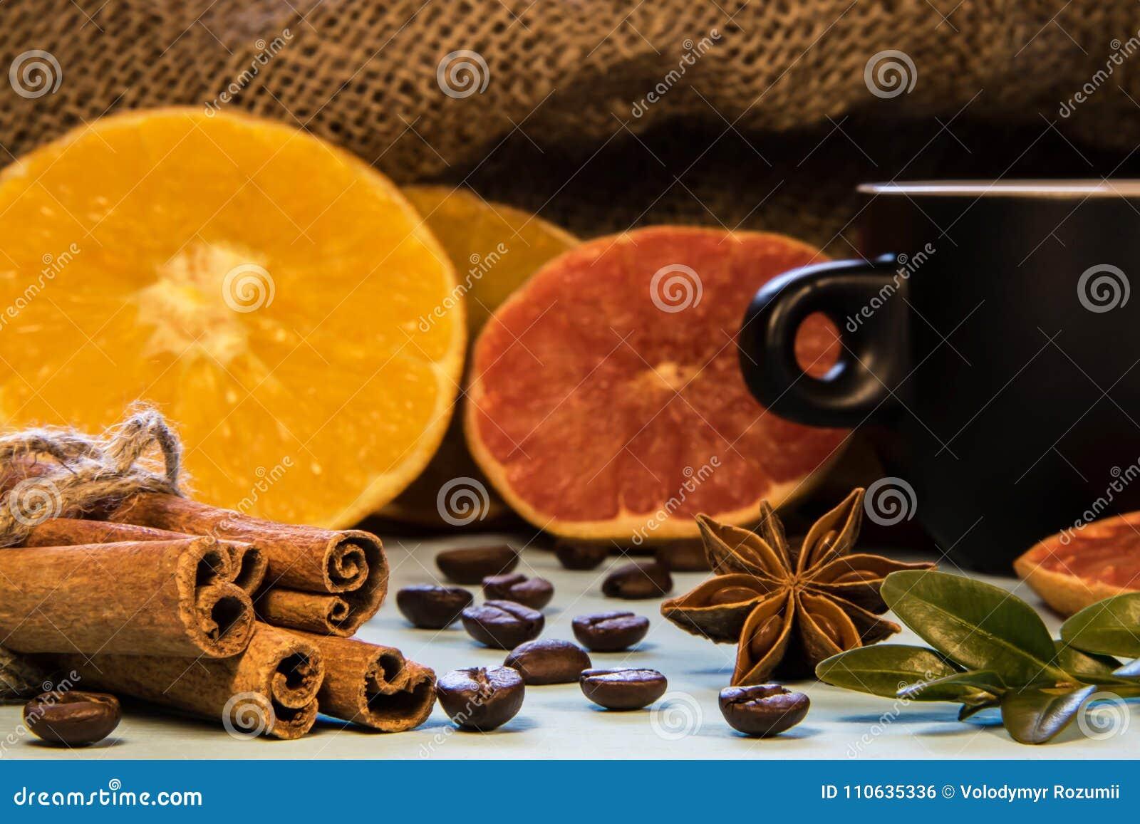 Una tazza nera di caffè accanto a cannella con i budini e le arance tagliate