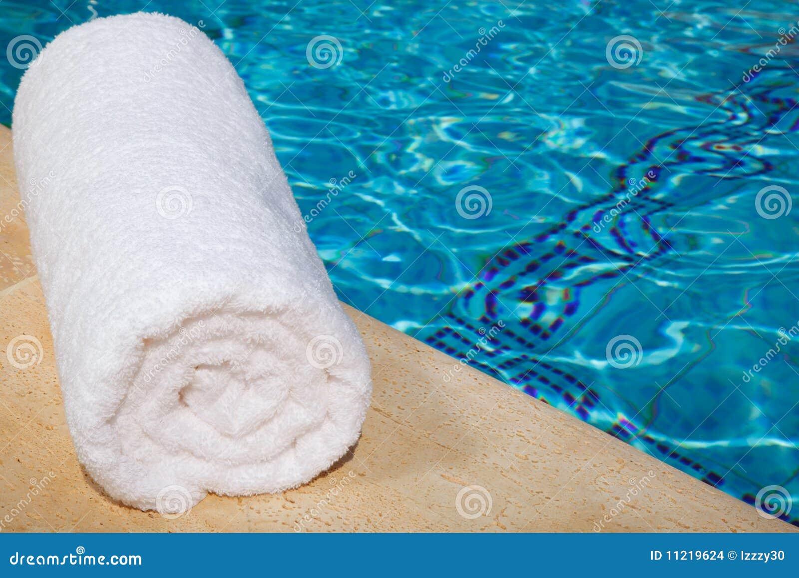 una toalla blanca enrollada por la piscina azul imagenes de