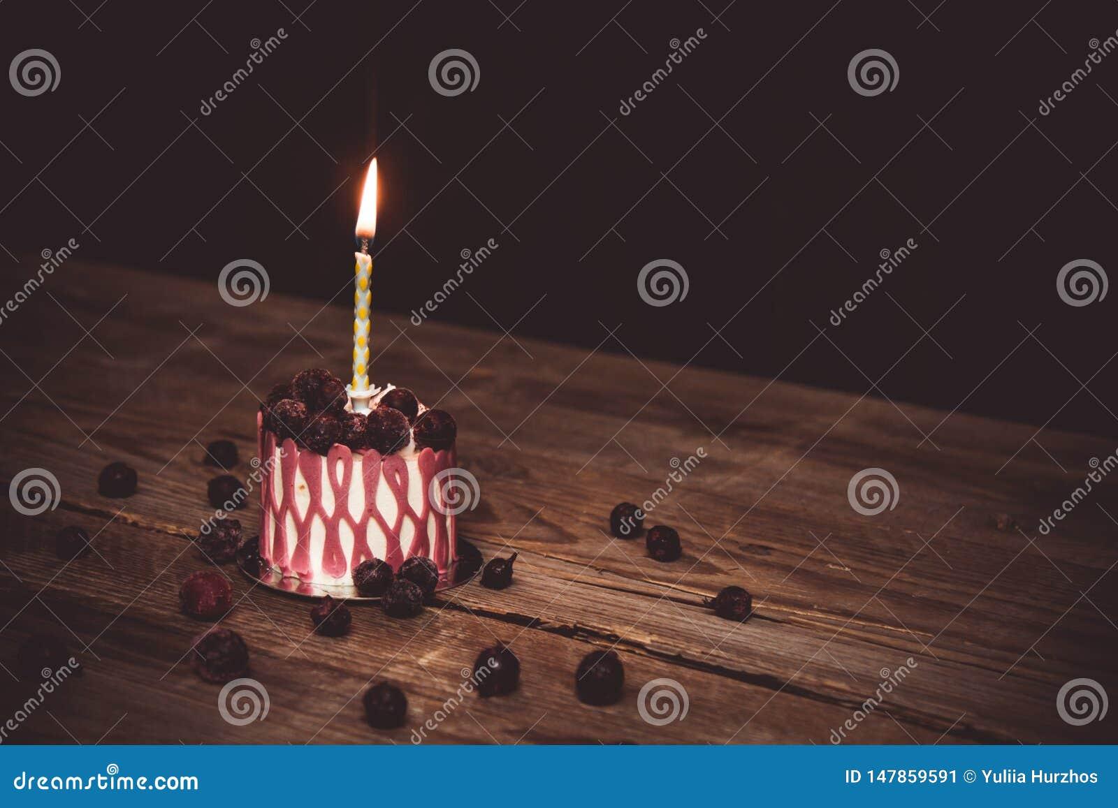 Una vela ardiendo en una torta festiva de la torta con las frutas de la cereza en una tabla de madera r?stica en un fondo oscuro