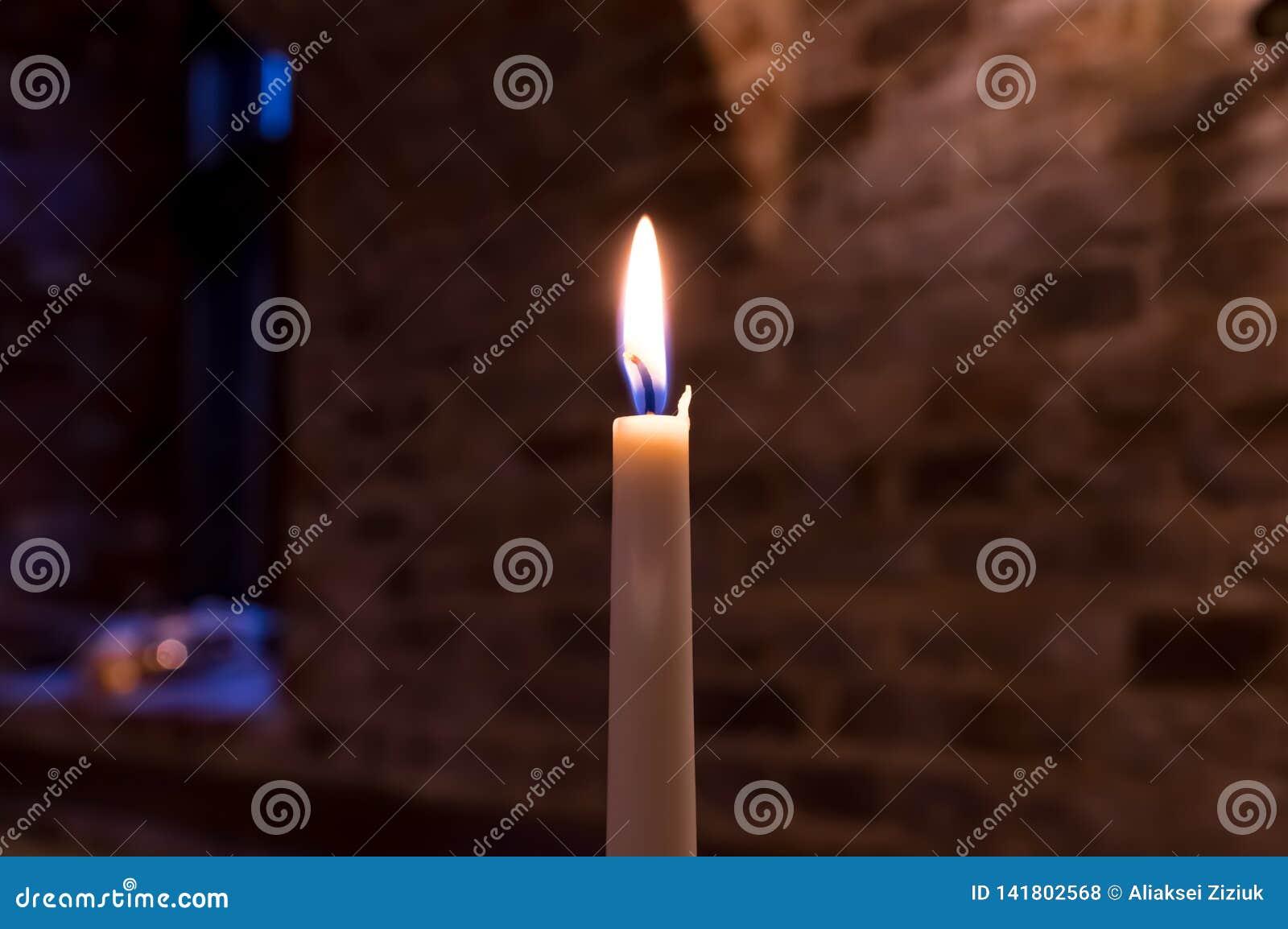 Una vela ardiente contra la pared de un ladrillo