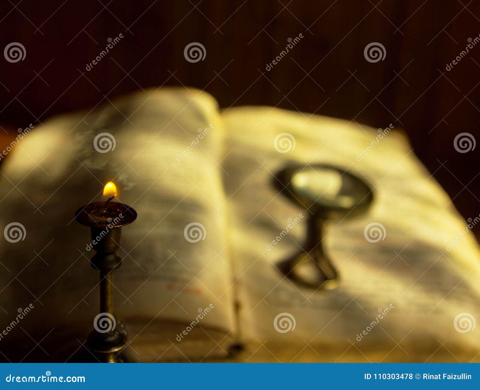 Una vela de muerte y un libro viejo con una lupa