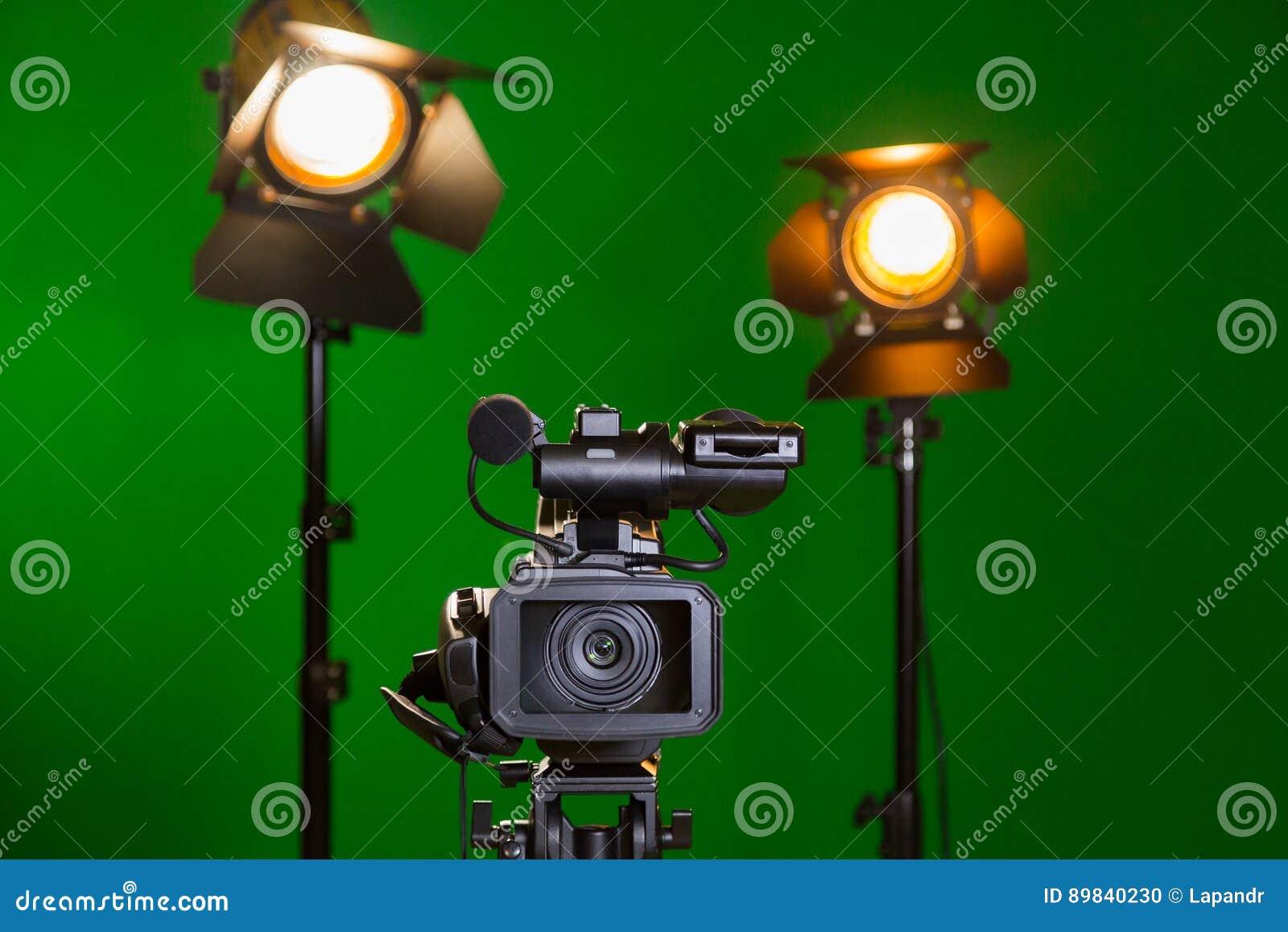 Una videocamera e un riflettore con una lente di Fresnel su un fondo verde Contaminazione nell interno La chiave di intensità