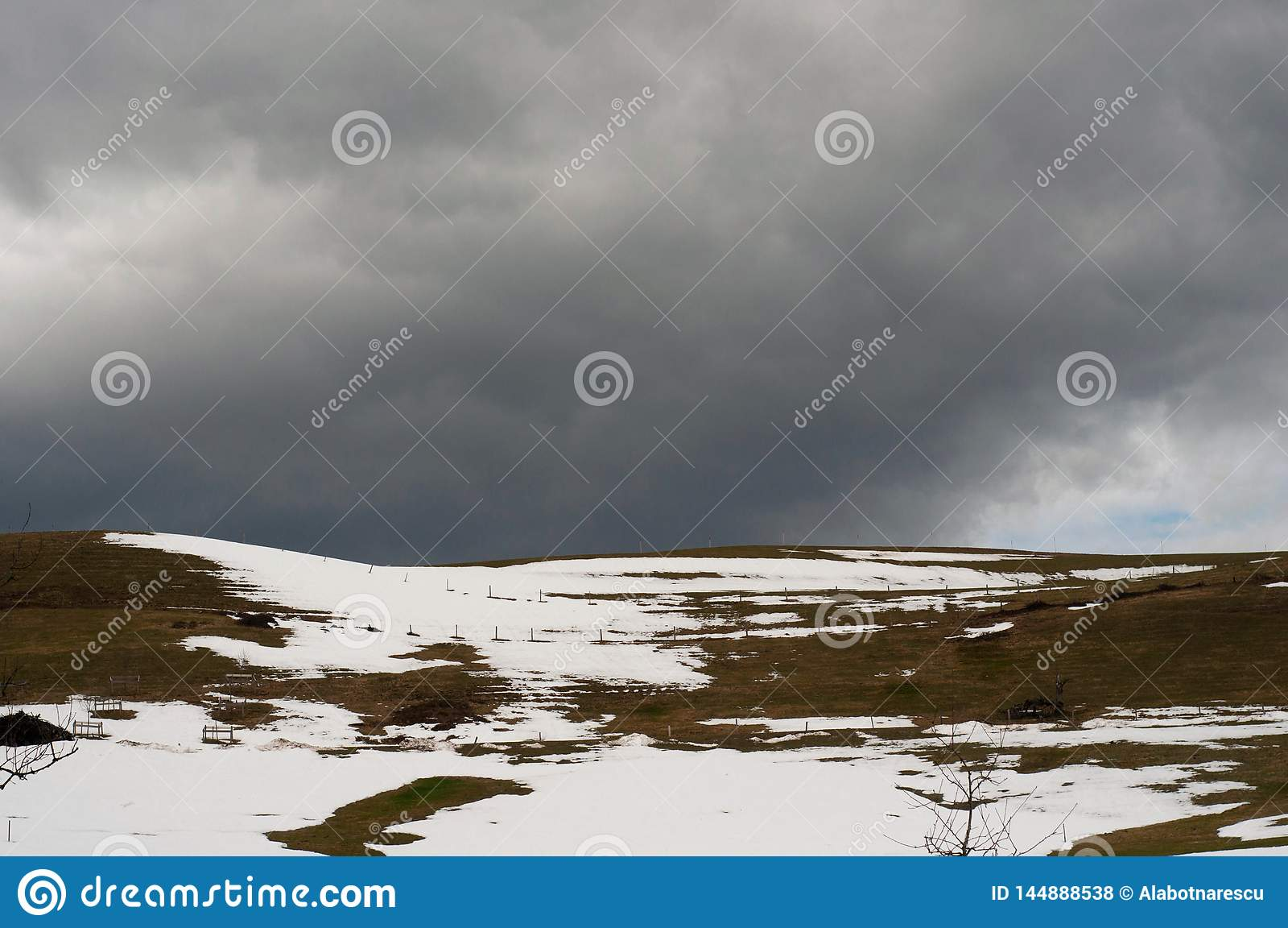 Una vista della campagna di una collina con erba verde coperta di neve all inizio d aprile