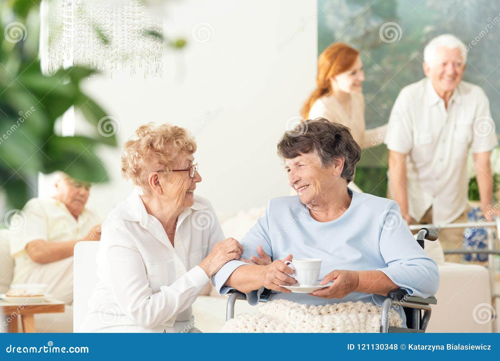Una vista frontale di due donne geriatriche felici che parlano e che tengono mano