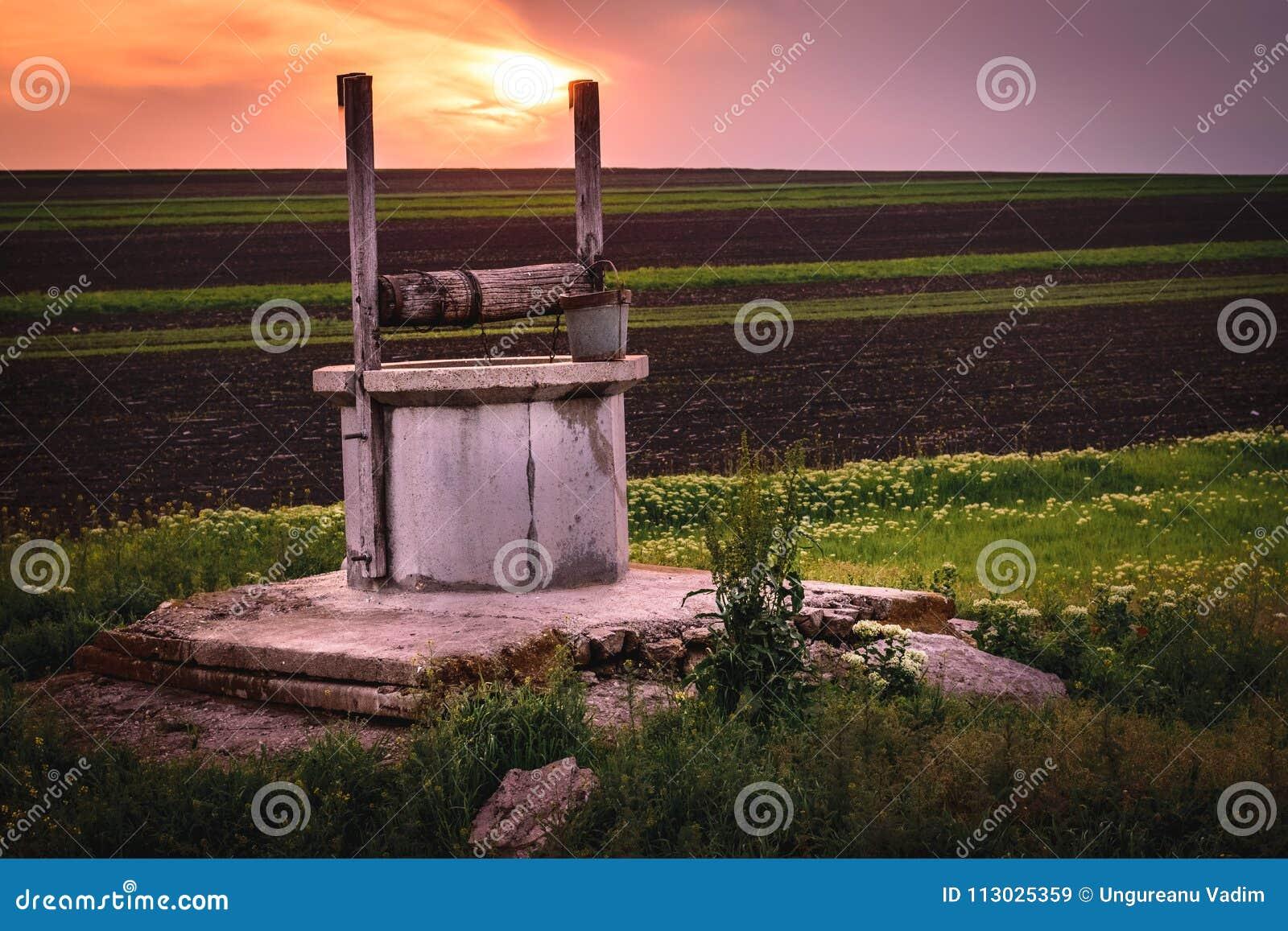Una vista a un pozo de drenaje cerca un campo durante amanecer