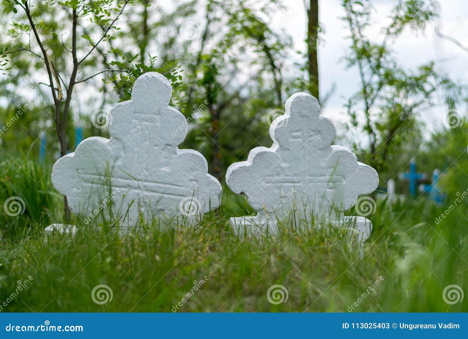 Una vista a 2 viejas cruces blancas en un cementerio