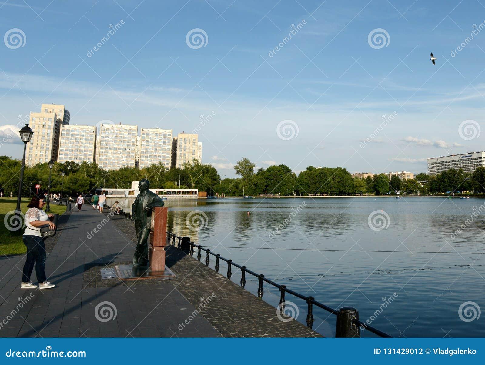 Unbekannte Frau am Monument zum Erfinder des Fernsehens Vladimir Zvorykin auf der Bank des Ostankino-Teichs