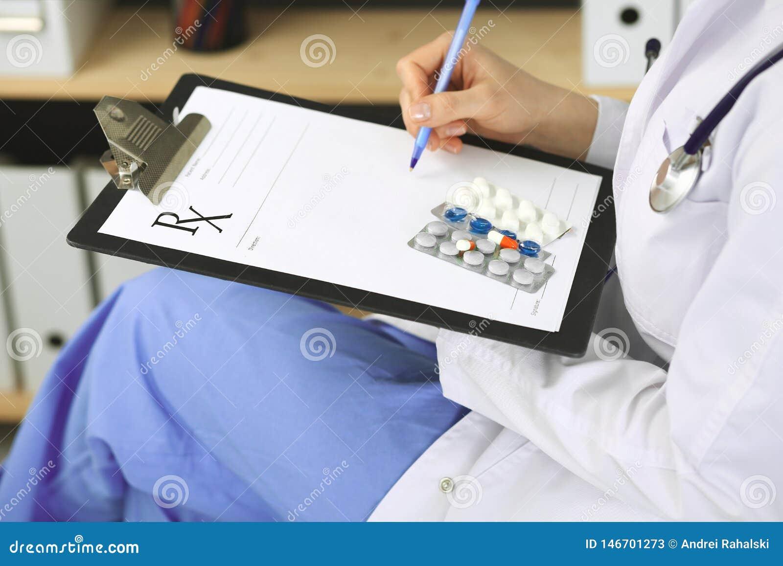 Unbekannte ?rztin bei der Arbeit am Krankenhaus Pillen am medizinischen Klemmbrett Junger weiblicher Arzt Verordnung schreiben od