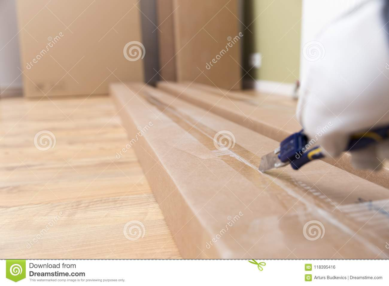 Unboxing Of Cardboard Box Of New Furniture With Construction Knife Moving To New House Purchase Of New Furniture Stock Photo Image Of Package Flat 118395416