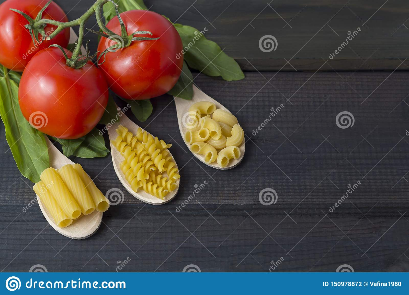 Uncooked pasta in a wooden spoo