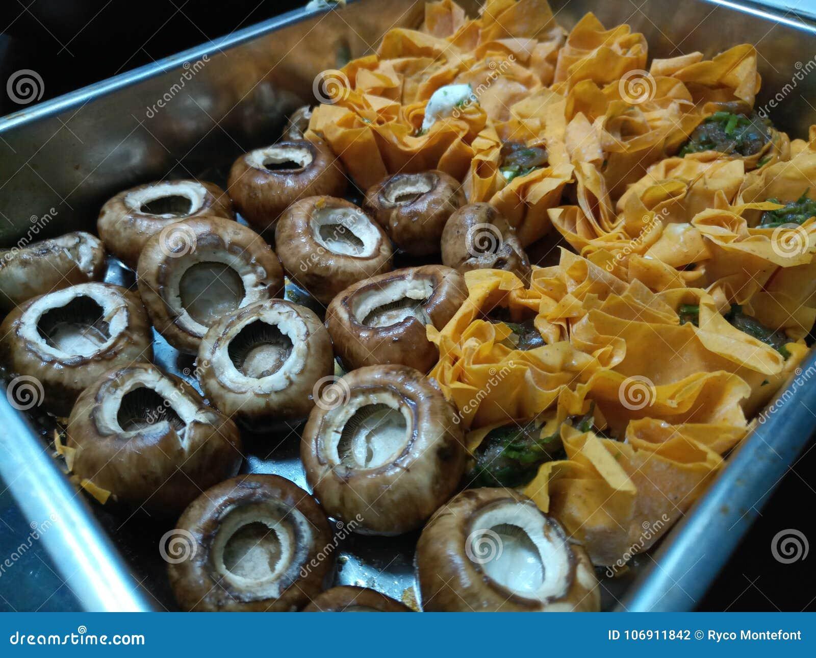 Uncooked pieczarek i kózek sera tartlets w srebnej tacy