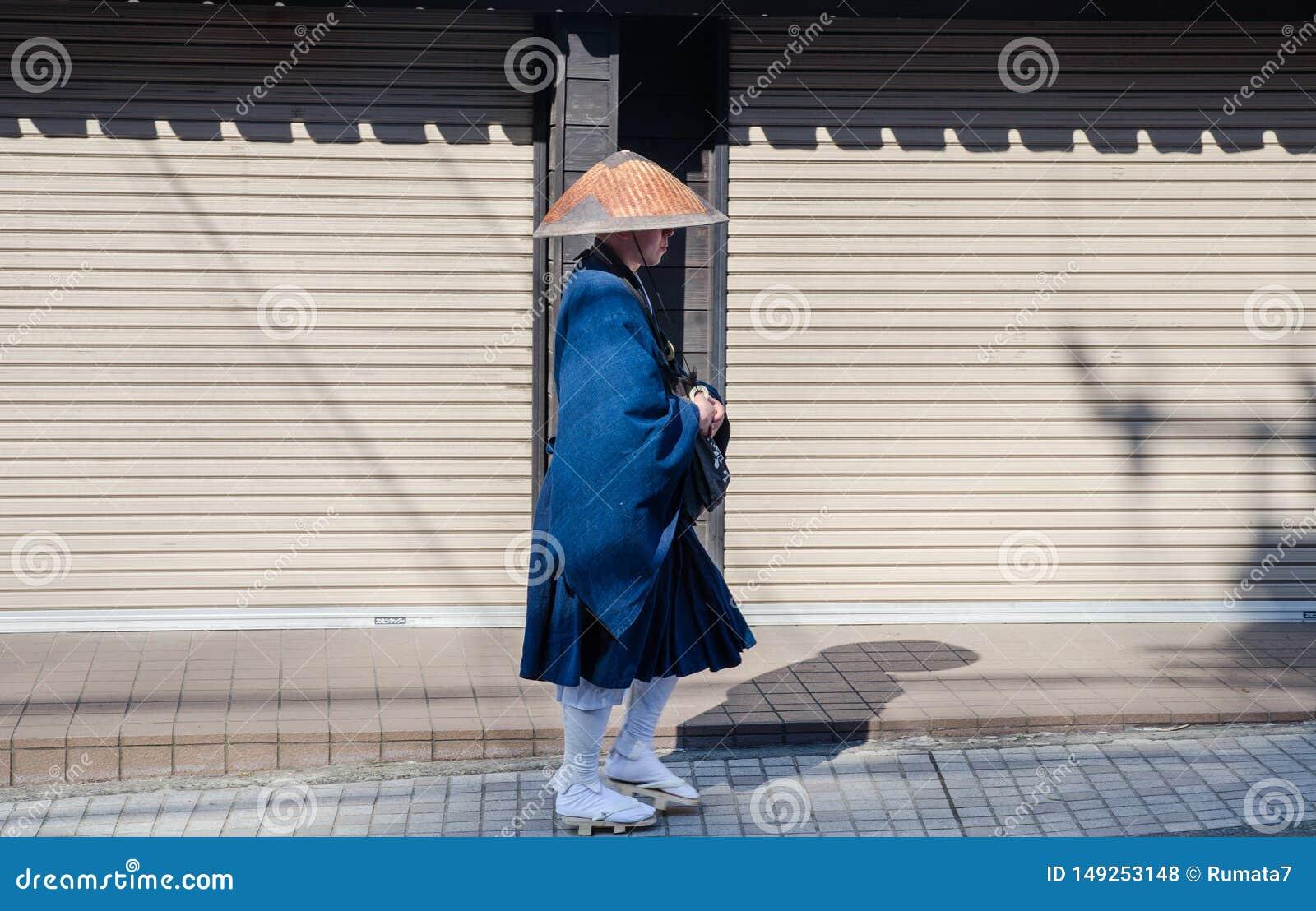 Undefined japanese monk walk on Kamakura`s city street